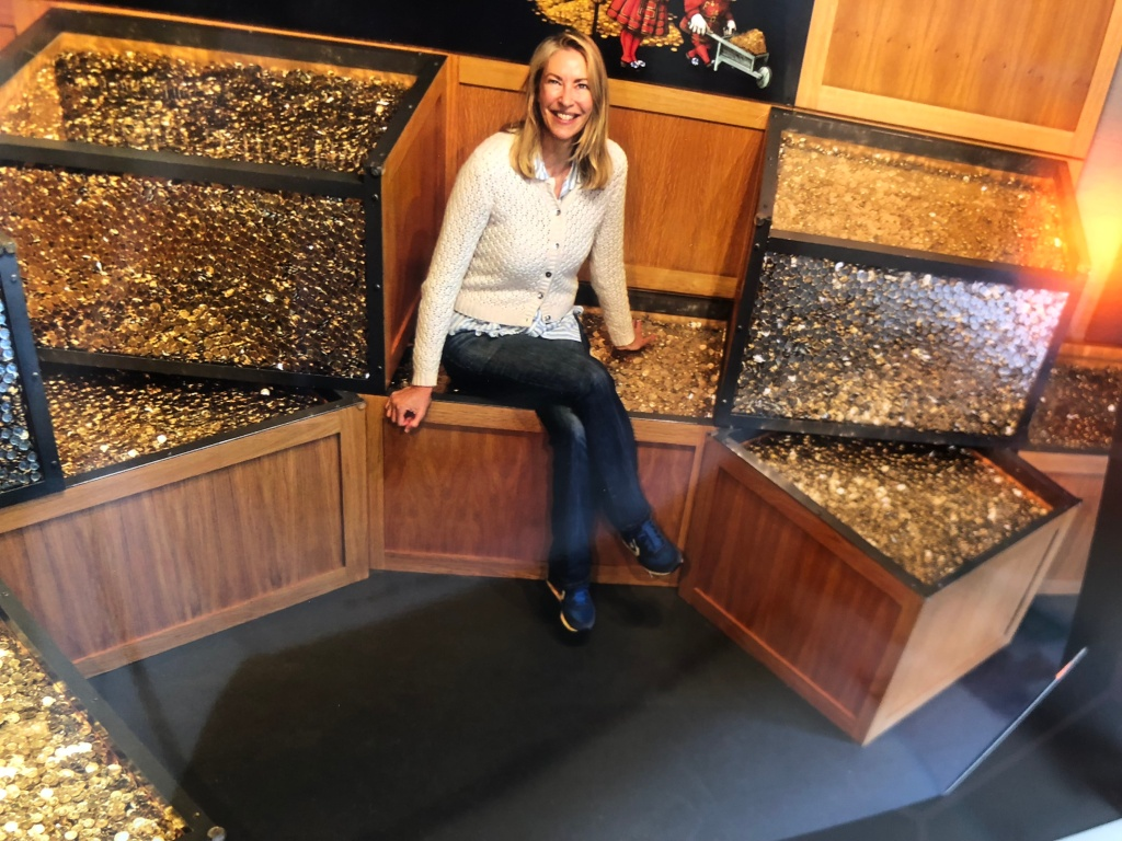Author Linda Davies at The Royal Mint Llantrisant, surrounded by chests of money